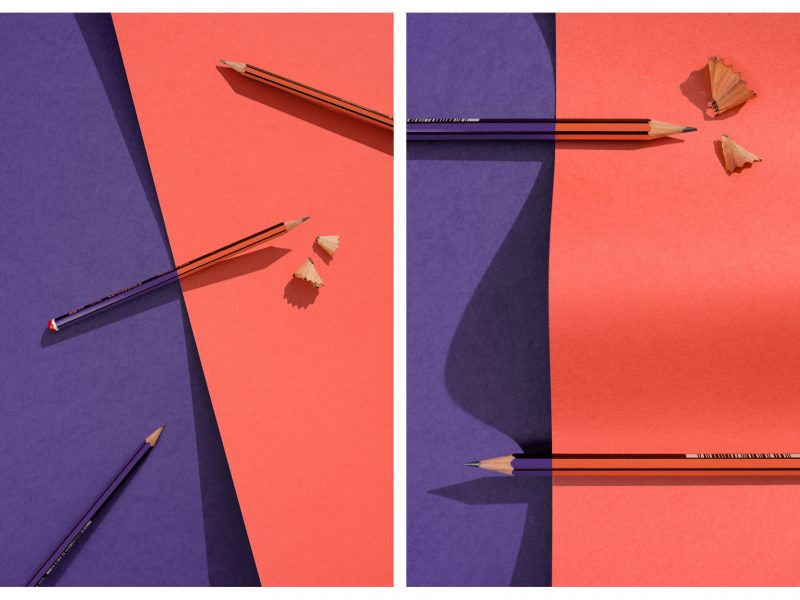 Creative photography of HB pencils on coral and violet paper
