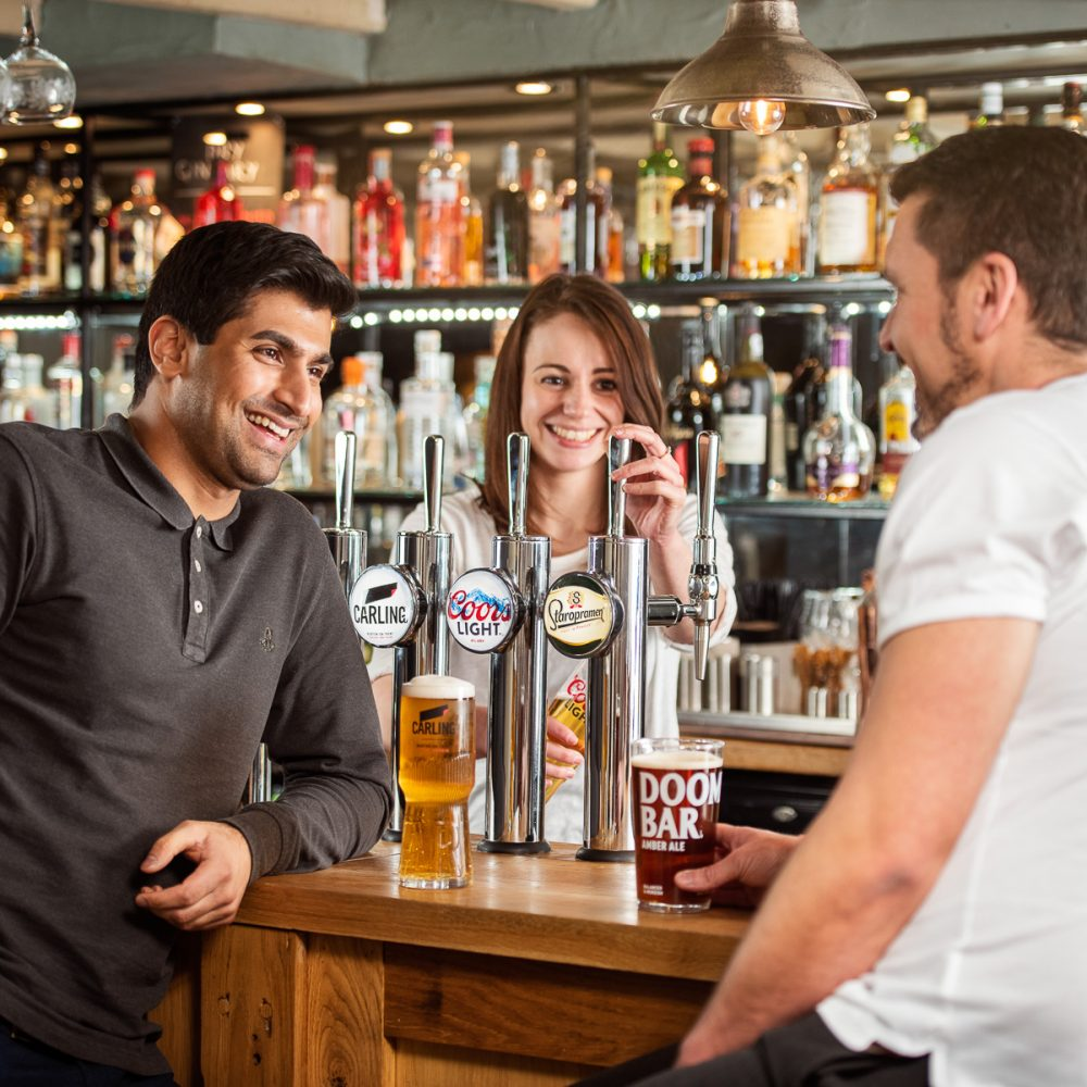 Two man chatting at the bar over a pint of Carling and Doom Bar