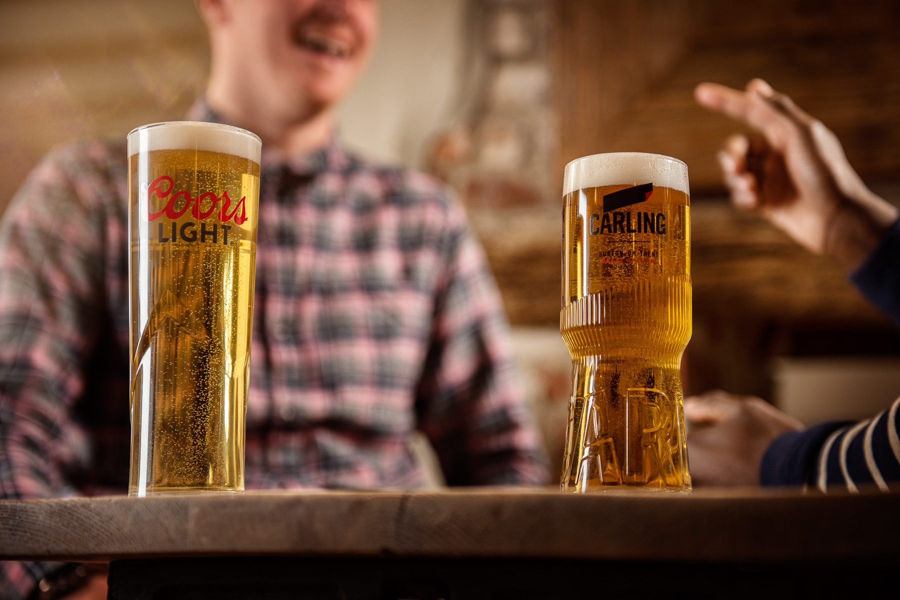 Coors light and Carling pints or larger on a table in a pub setting