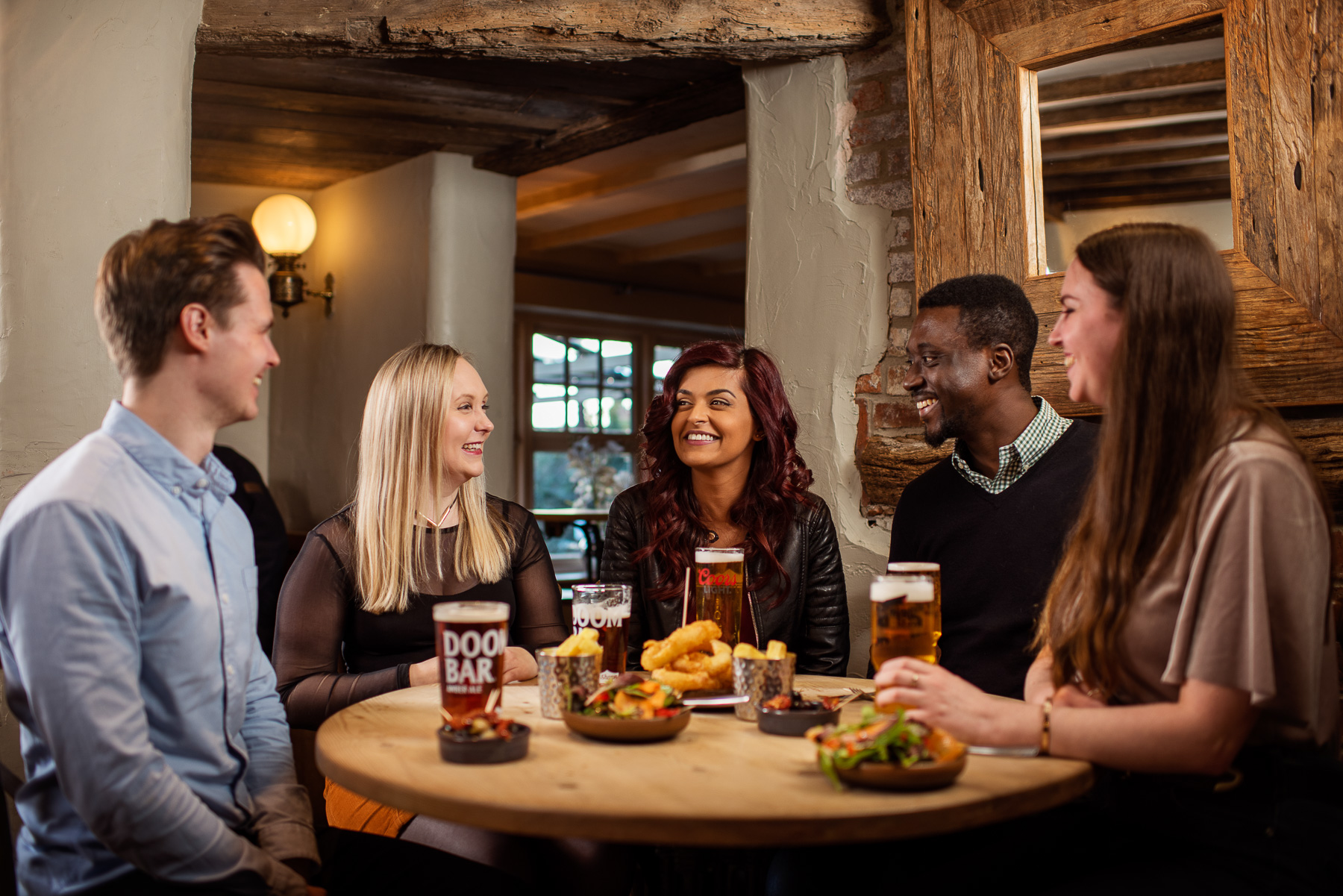 Group of young men and women meet in the pub for a social drink and food