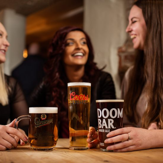 A group of women socialise in the pub with Coors Light, Doom Bar and Staropramen