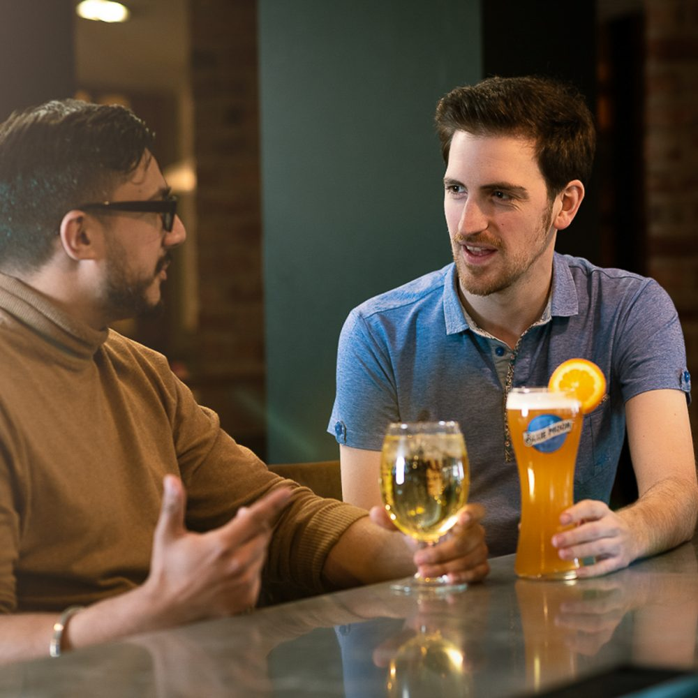 Two men having a chat in a pub with Blue Moon and Aspall Cider