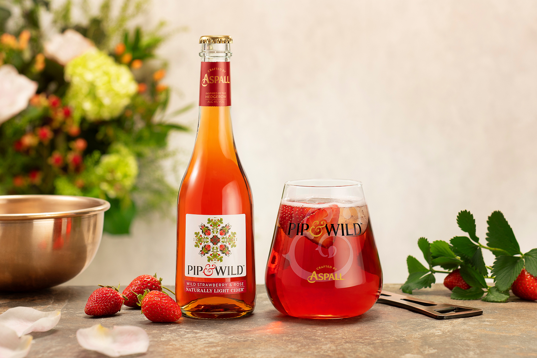 Pip & Wild cider bottle and glass on a stone table with strawberry garnishes