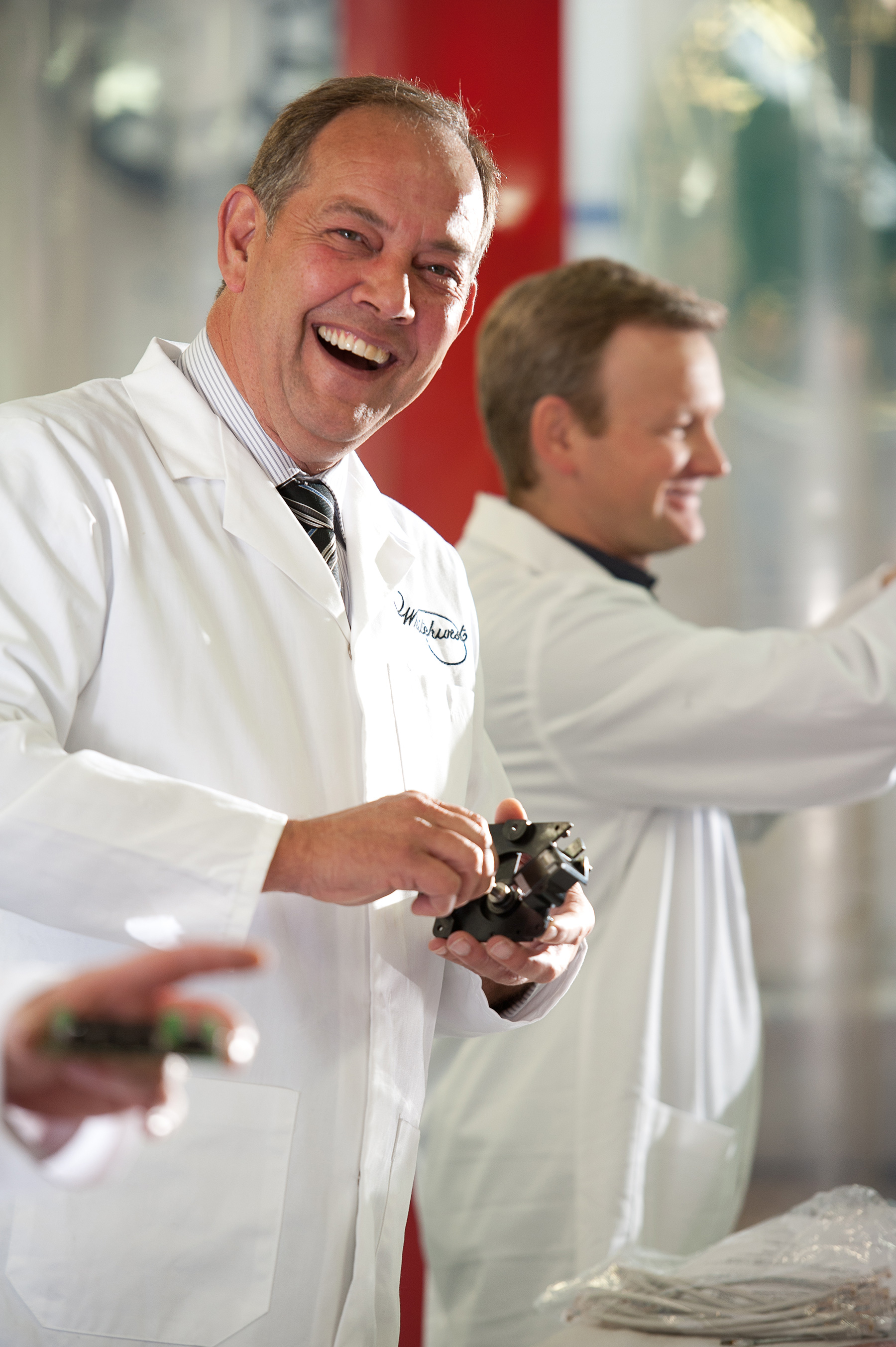 Man is smiling wearing white laboratory jacket whilst working