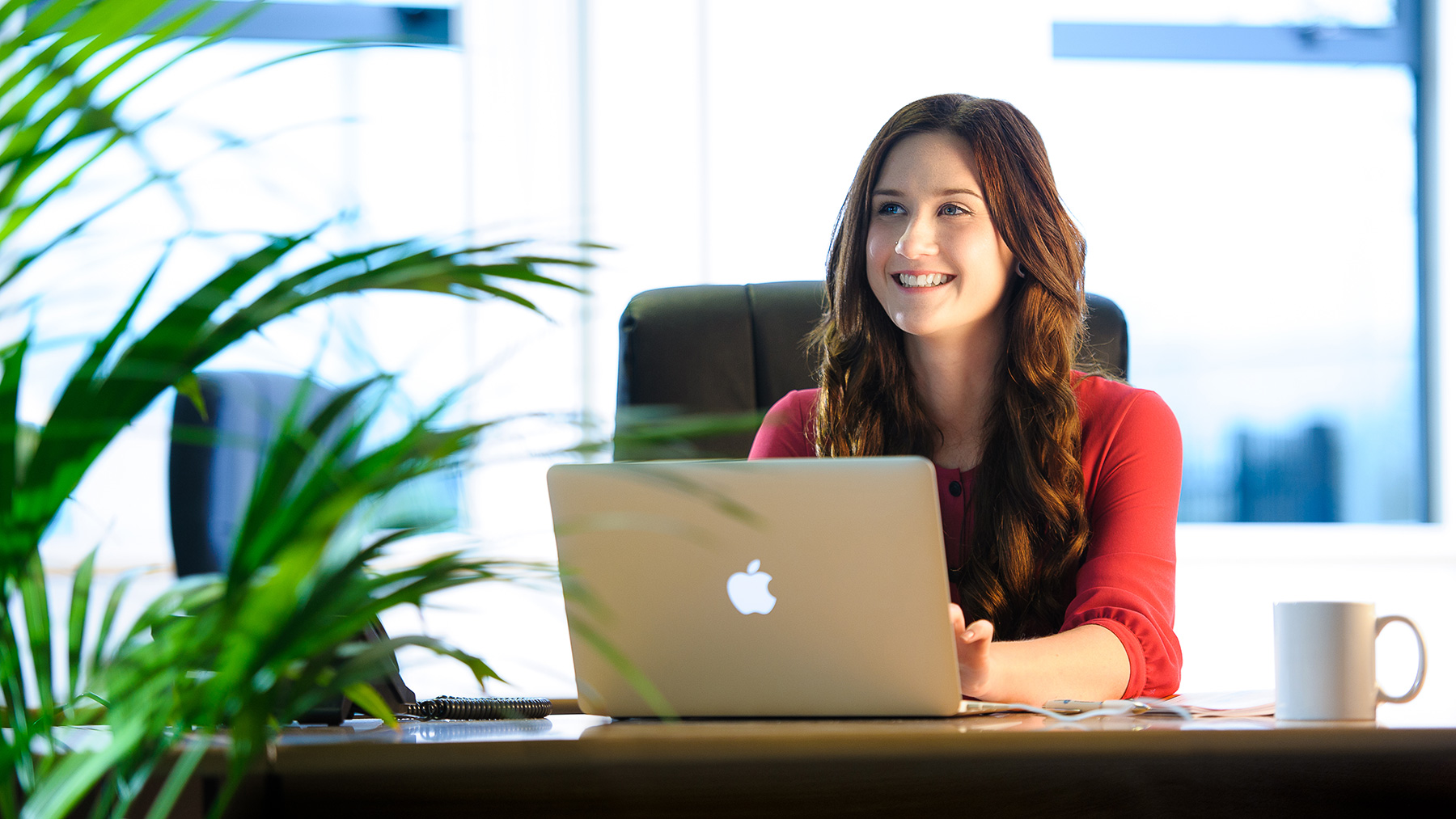 young women in a red top works happily at her mac with mug on the desk