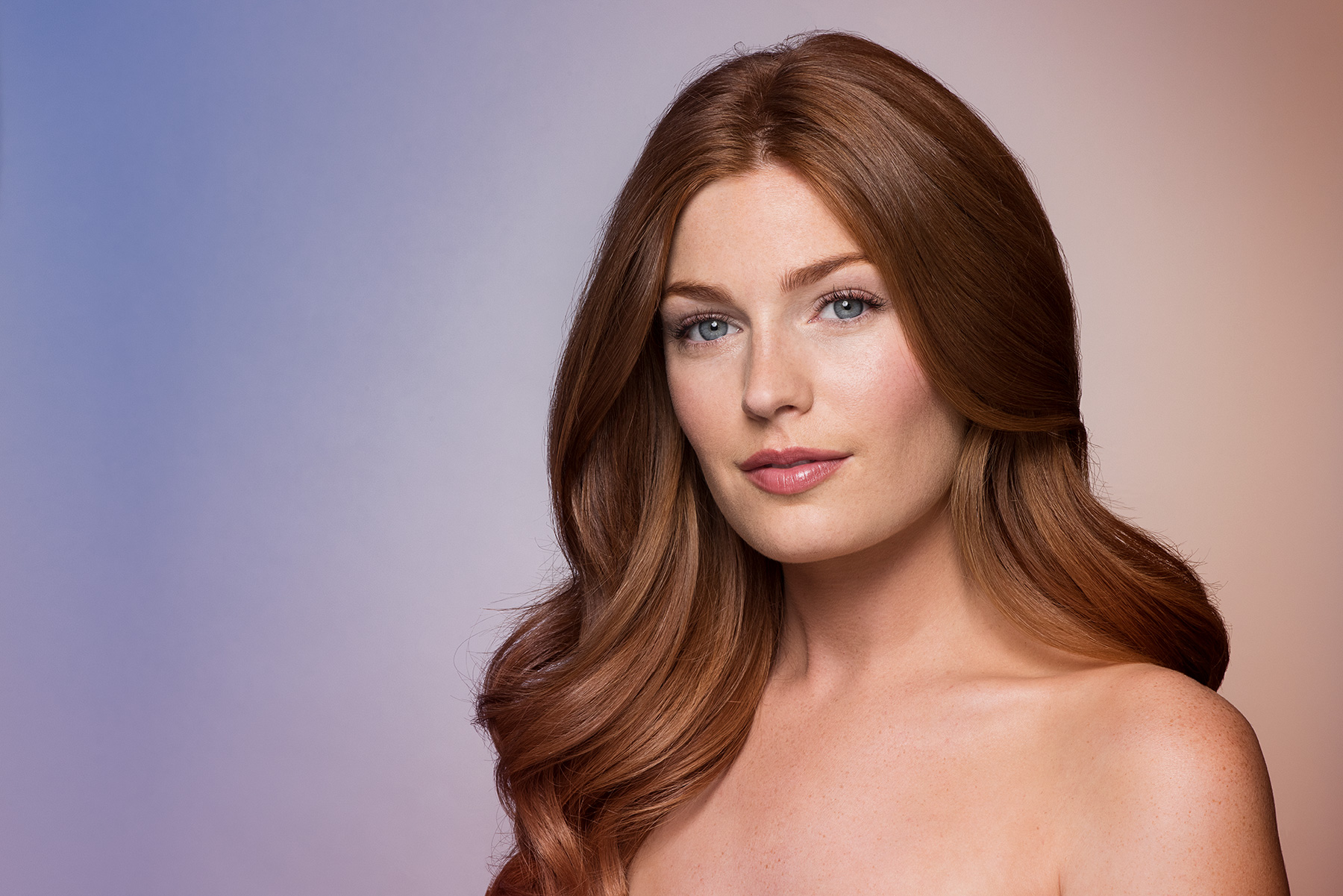 Studio portrait of model with wavy auburn hair. Photographed with a lilac and nude gradient background