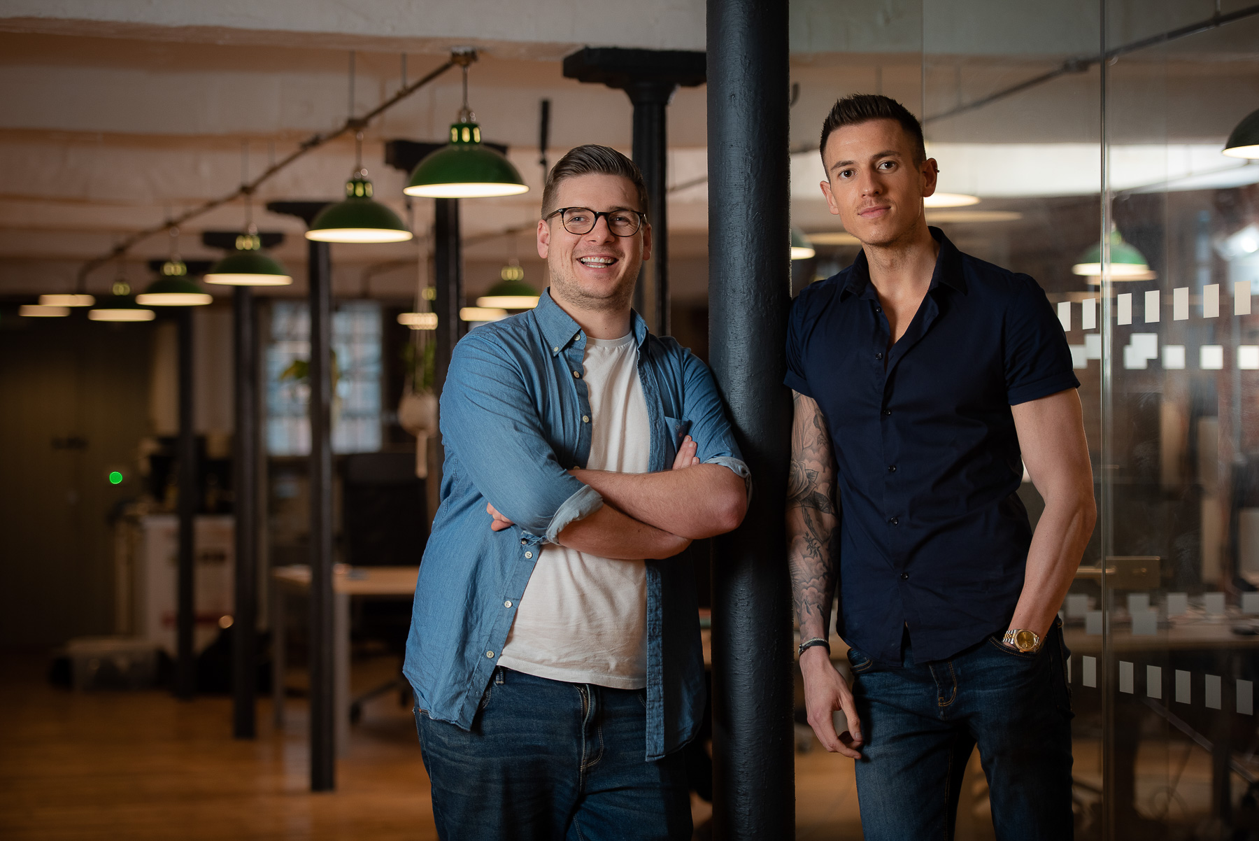 Directors of company lean on post at their trendy office