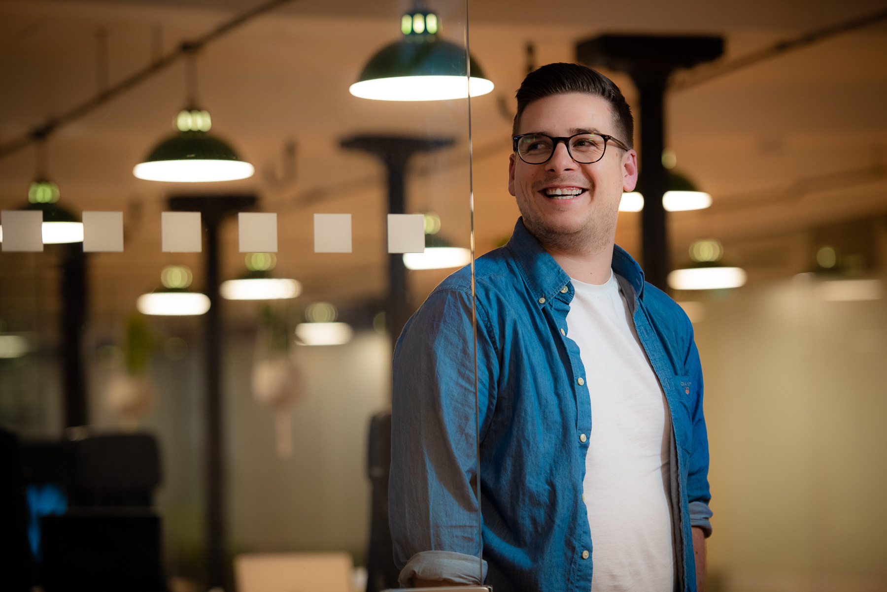 Young professional web developer leans on glass at trendy office