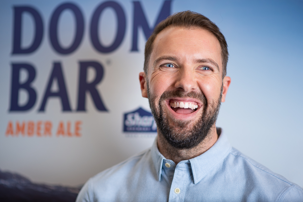 Corporate headshot of smiling young professional photographed at Molson Coors, Burton-on-Trent