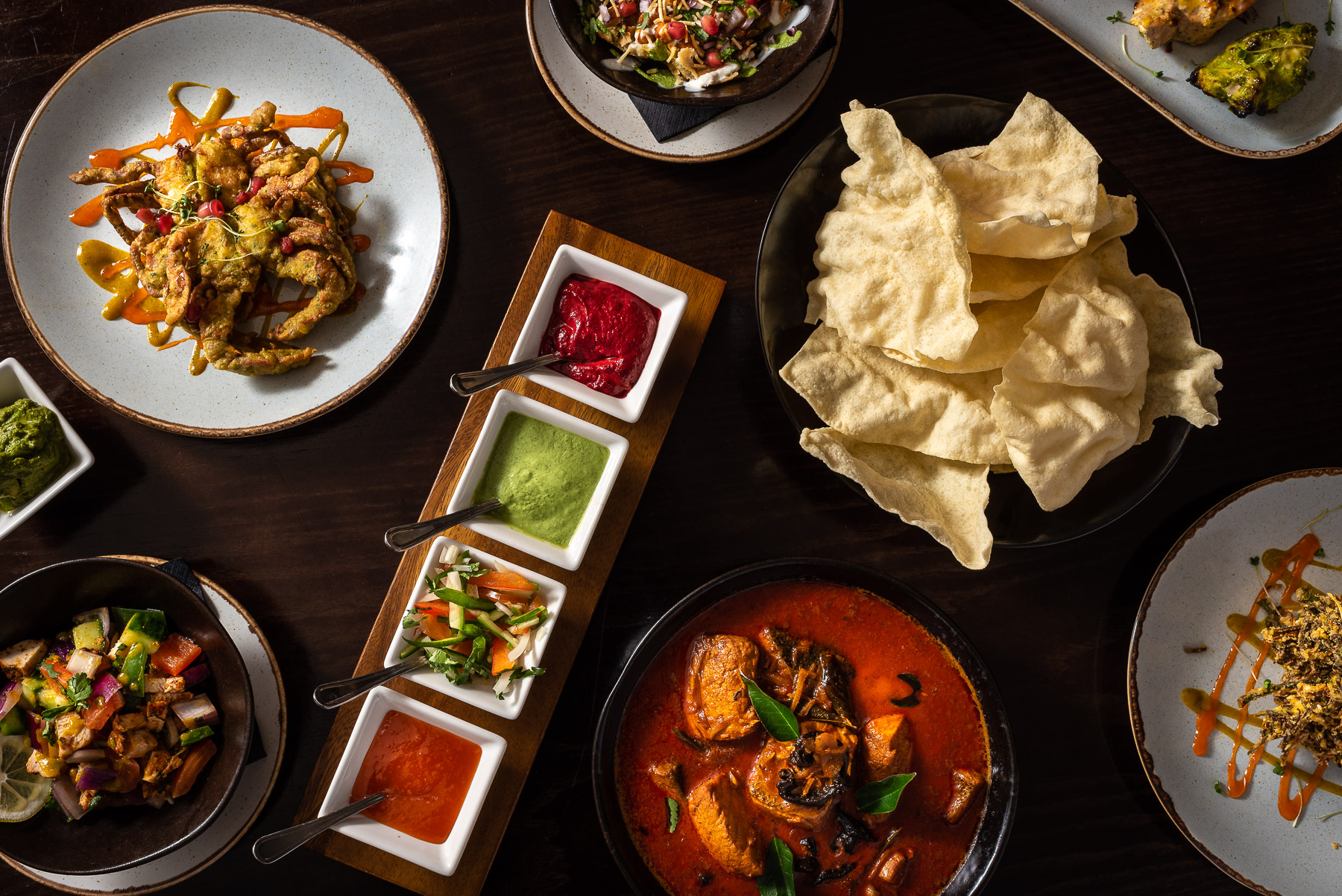 Top down image of colourful indian food on dark wood table