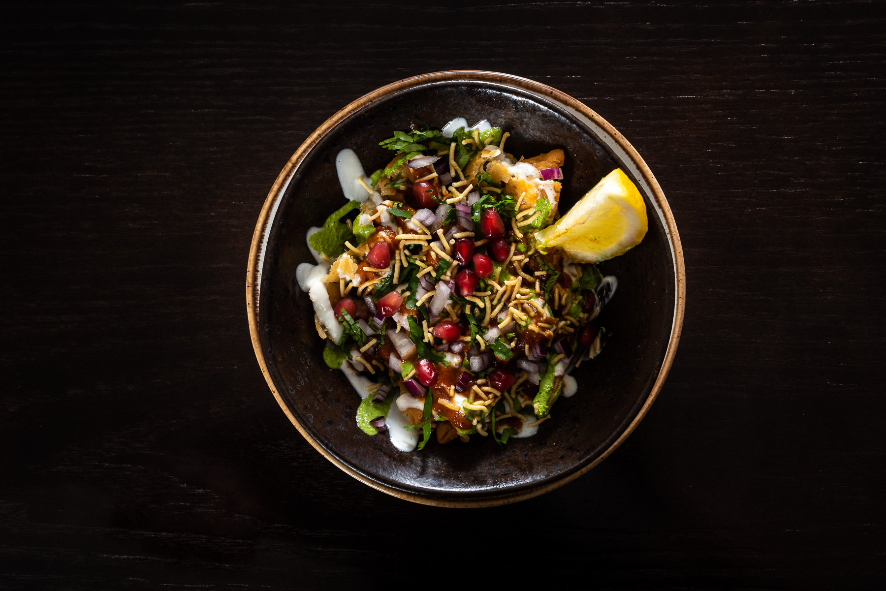 Top down image of an Indian salad with fresh lemon on dark wooden table