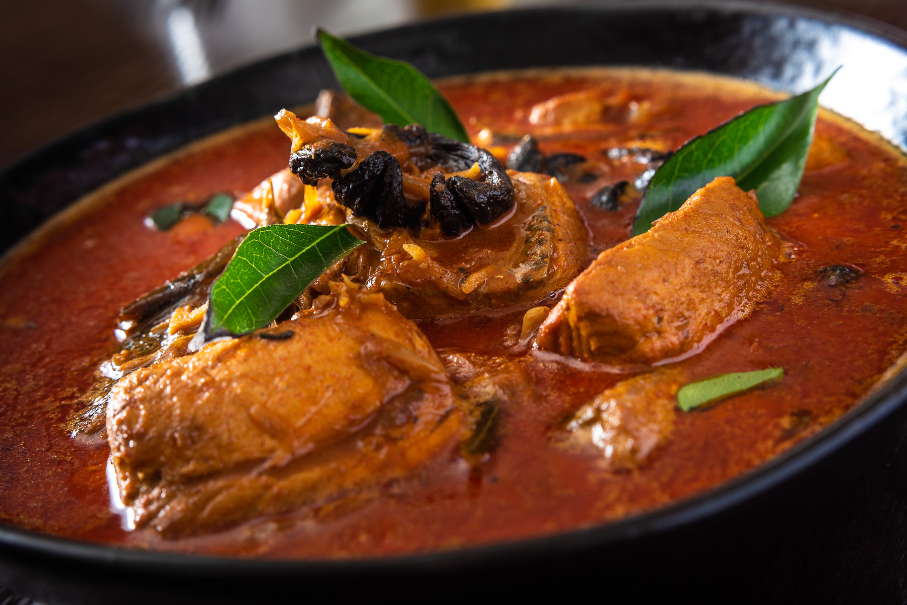 Close up of rich red chicken curry on dark wood table top
