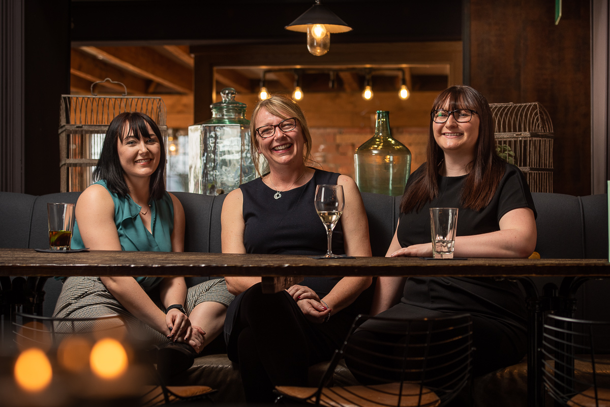 Group image for Wathall's behind a wooden table in a low lit bar