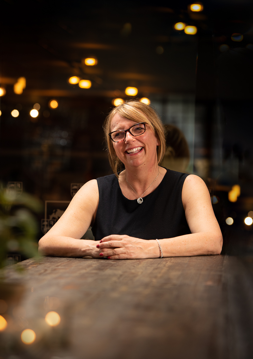 Helen Wathall MBE photographed at a large wooden table in low lit venue