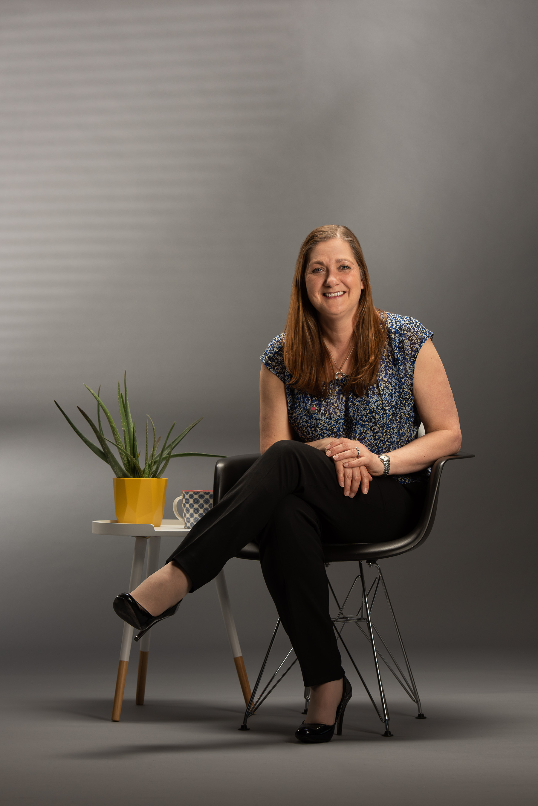 Portrait photograph of business owner sitting on a chair with table and plant pot