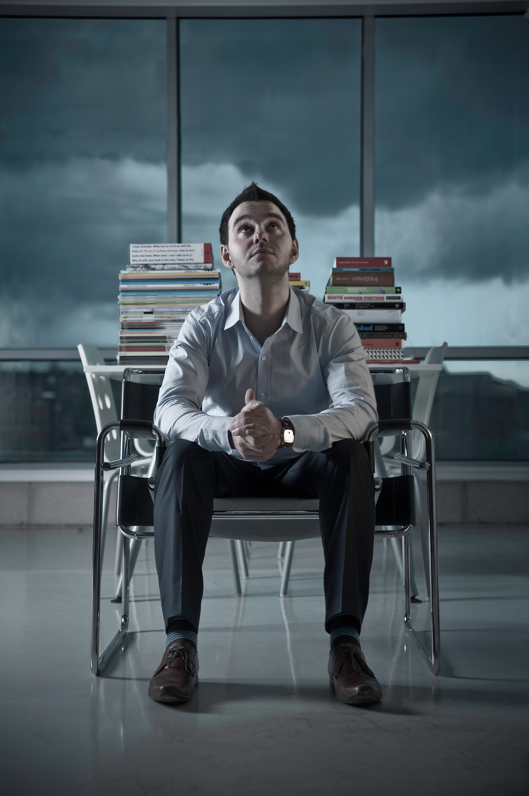Moody image of young professional man in modern office with grey cloudy sky behind