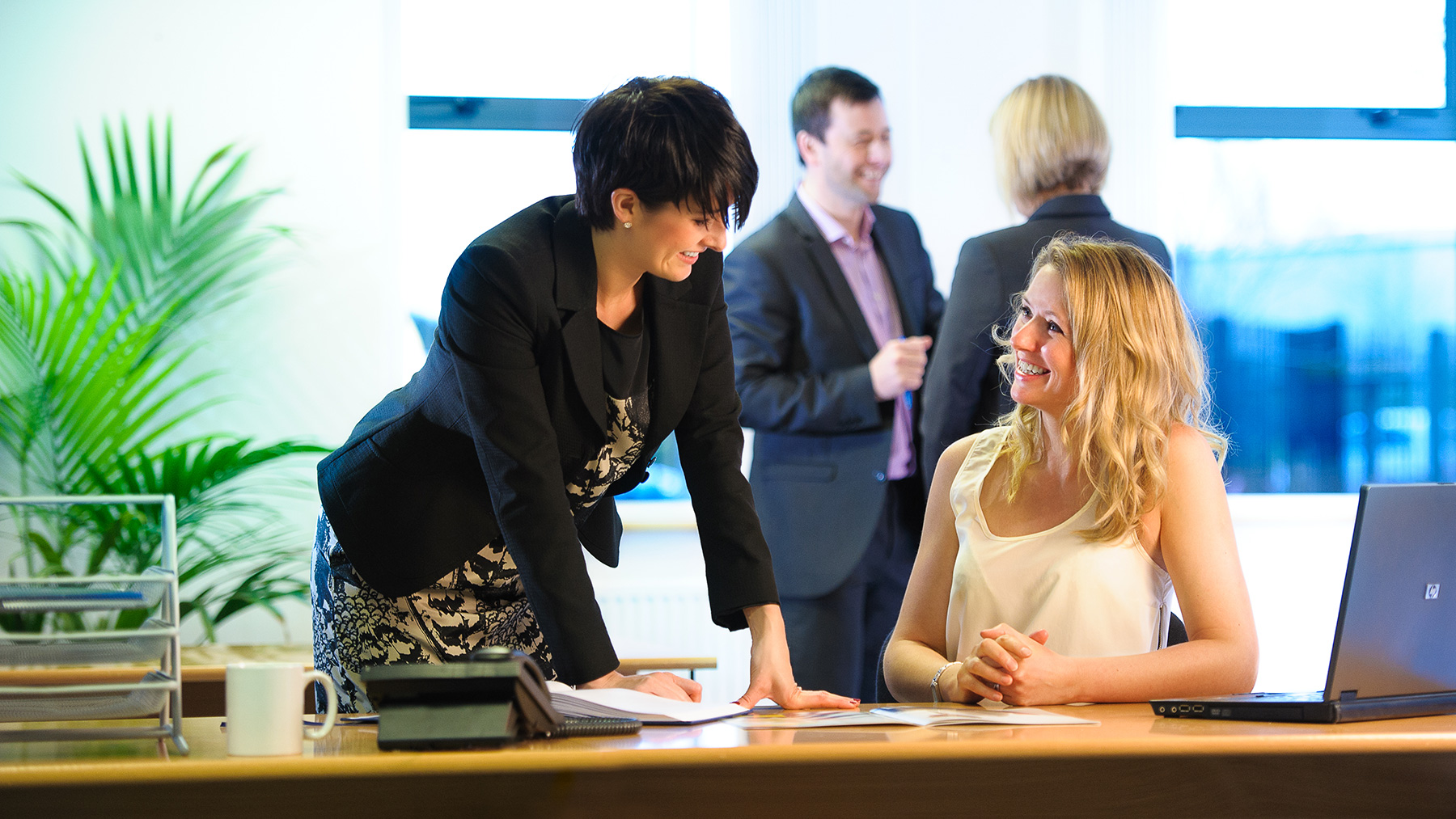 Two professional women interact in a bright and modern office