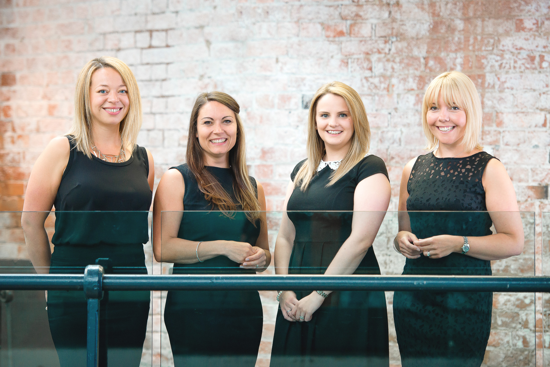 Group of young professional women in black business attire with natural brick background