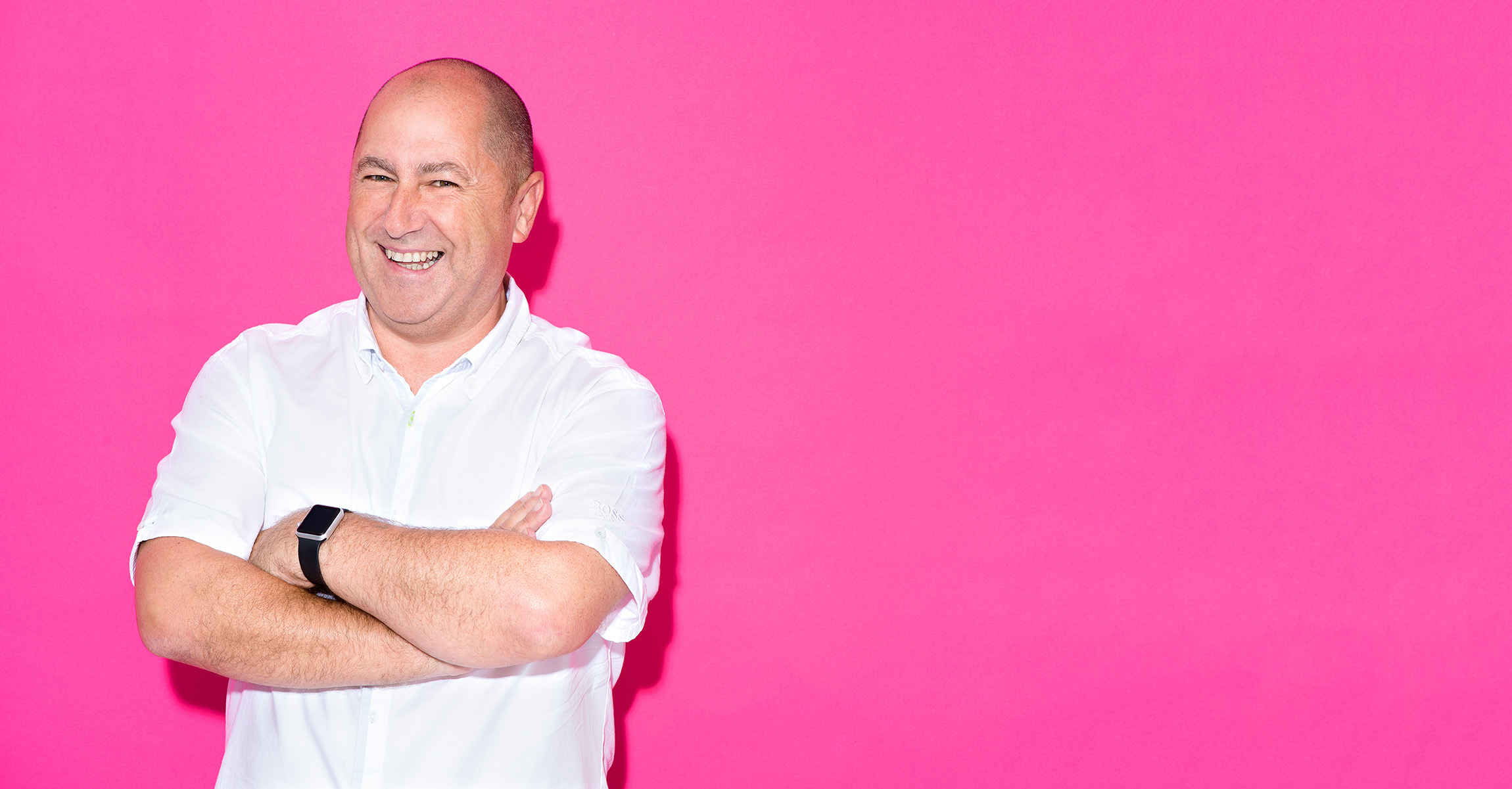 Man wearing casual white shirt photographed on bright pink background