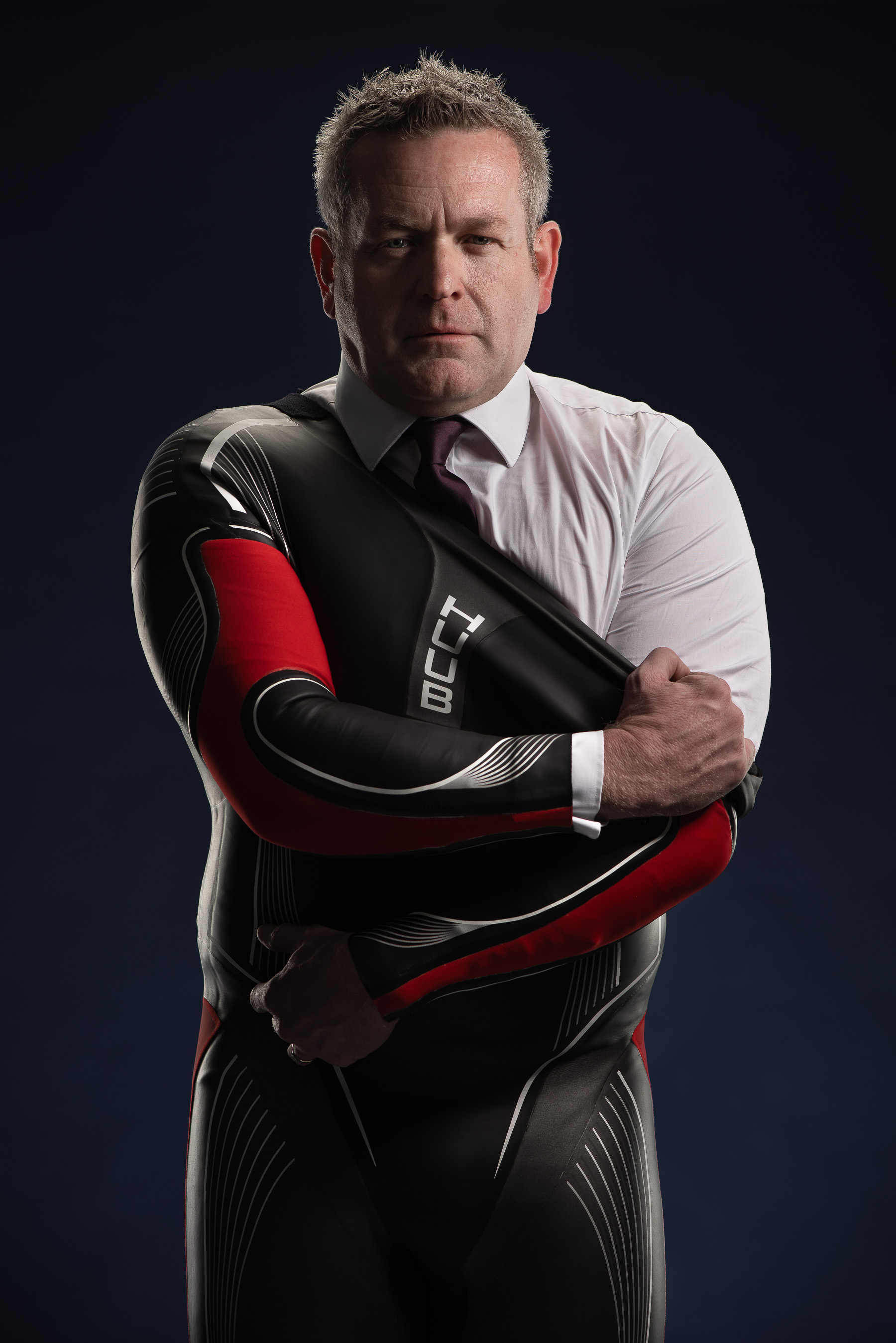Dean Jackson owner of HUUB ripping off wetsuit to reveal shirt and tie. Photographed on a dark navy background.