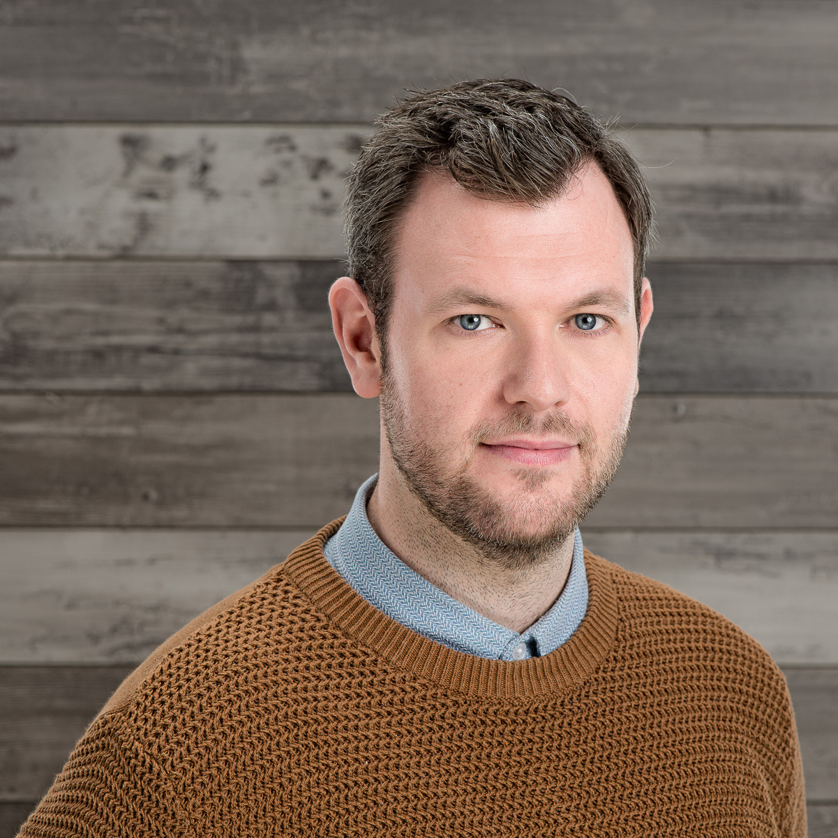 Young man in brown knit jumper photographed on a wooden background
