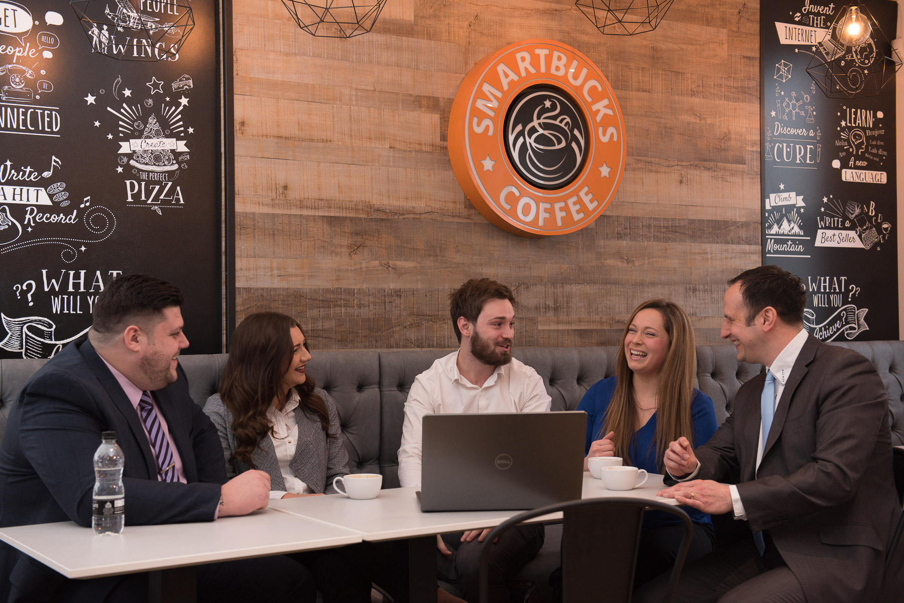 Team of young professionals laughing and interacting at an informal meeting at a coffee bar