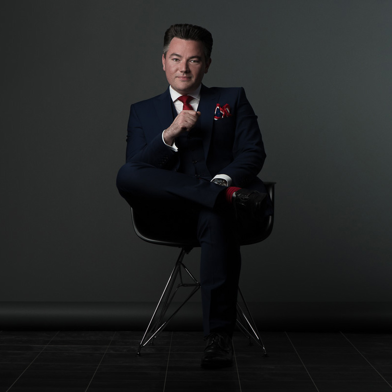 Studio portrait of a professional man sitting on a chair in a smart navy suit with red tie
