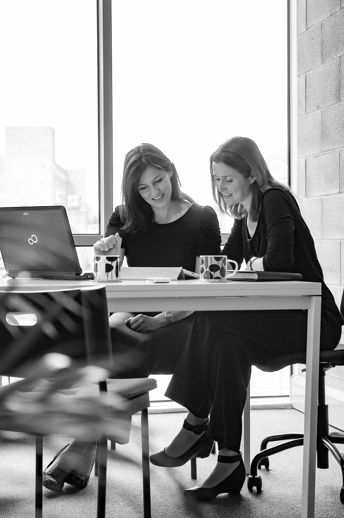 Black and white image of two women in a modern city office working together at a desk