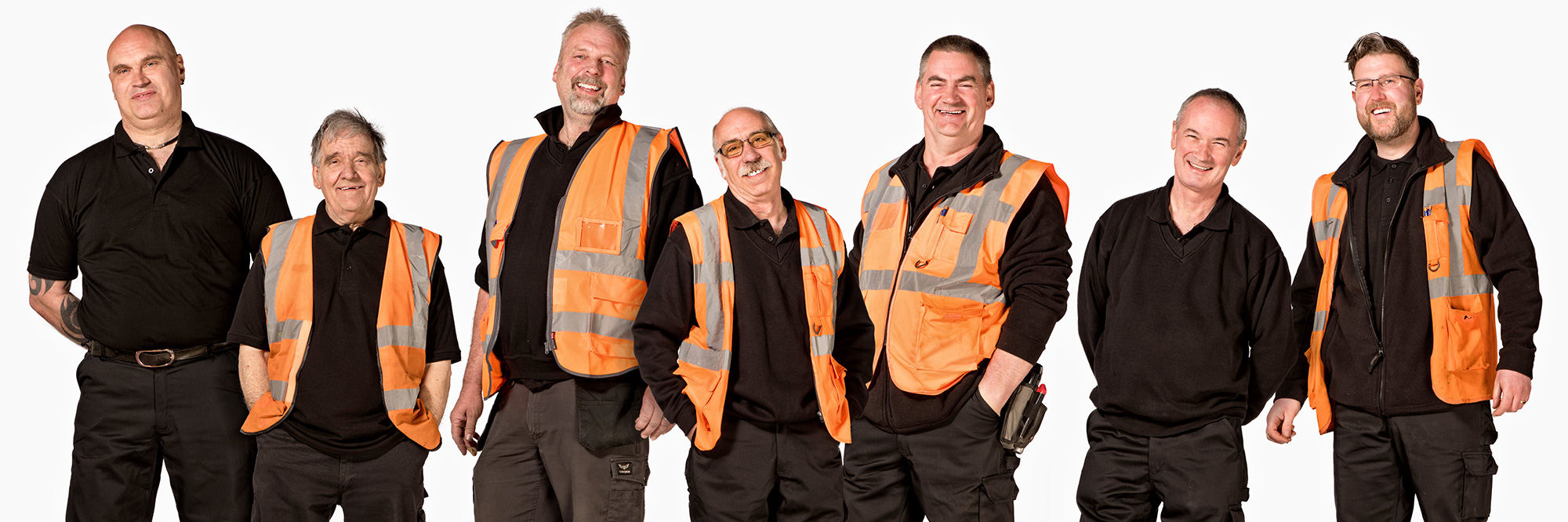 Group of warehouse workers on a white background wearing hi-vis jackets.