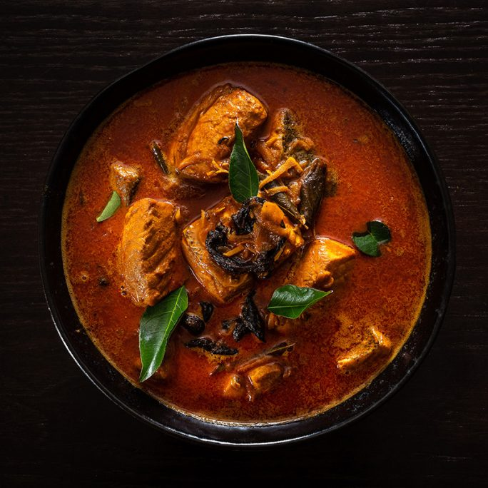 Round bowl of rich red chicken curry on dark wood table top