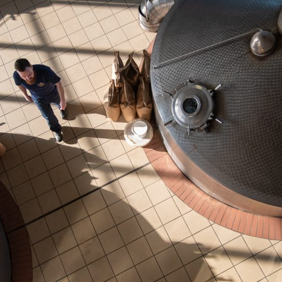 Arial view on man walking past tanks at brewery