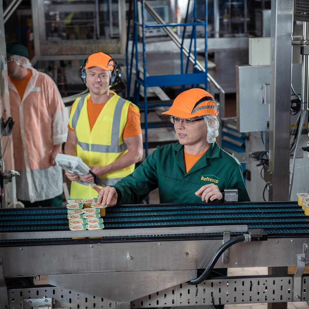 Happy team working at a production line at Refresco