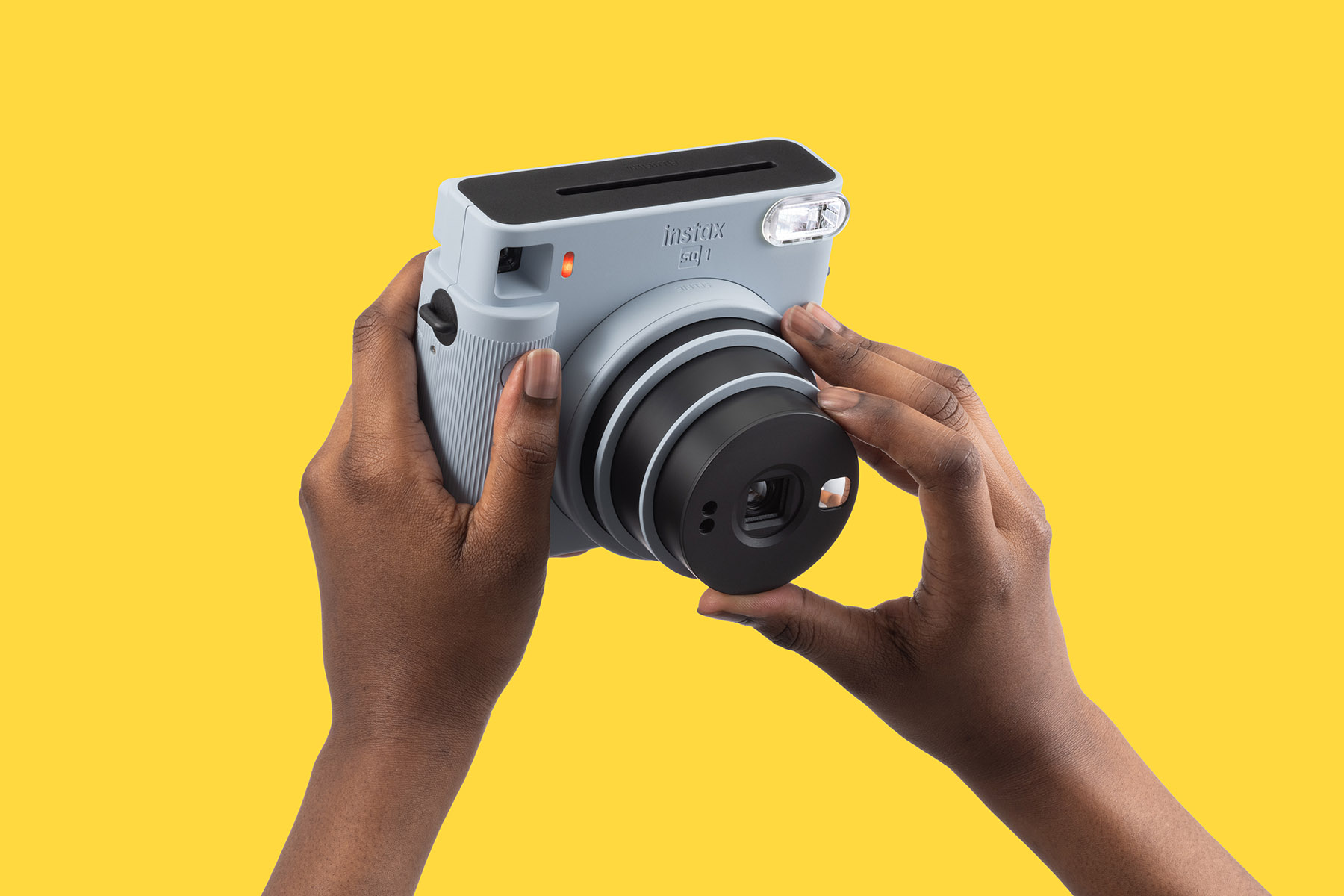Instax SQ1 with model holding on yellow background